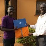 Murye Godfrey receiving a laptop from Bishop Joseph