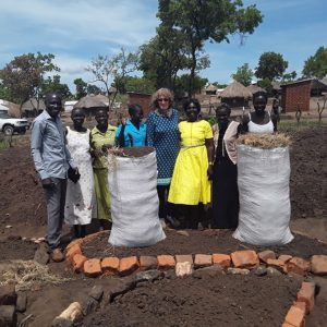 Here Livy is with members of the Emmanuel group based in Imvepi refugee camp. Jeska Kiden to her left, the group leader, proudly shows here the groups' small round key-hole shaped gardens and sack gardens.
