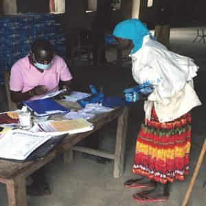 An elderly woman in Kerwa receiving her relief package
